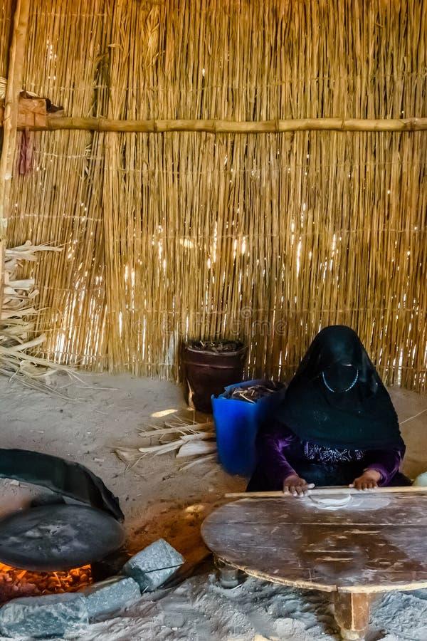 有被掩没的面孔的年轻回教妇女烹调在一所流浪的住宅的面包 库存照片
