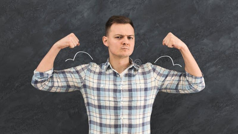 有被描述的肌肉的年轻人在黑板 免版税库存照片
