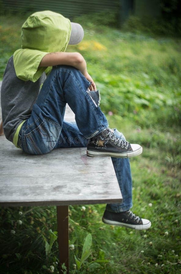 有被撕毁的牛仔裤的照片肮脏的无家可归的男孩 库存照片