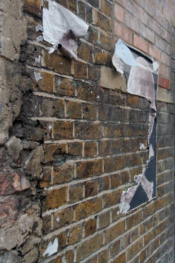 有被撕毁的街道海报的被暴露的被风化的砖墙 库存照片
