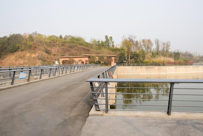 有被操刀的和涂焦油车行道的码头桥梁在晴朗的河 图库摄影