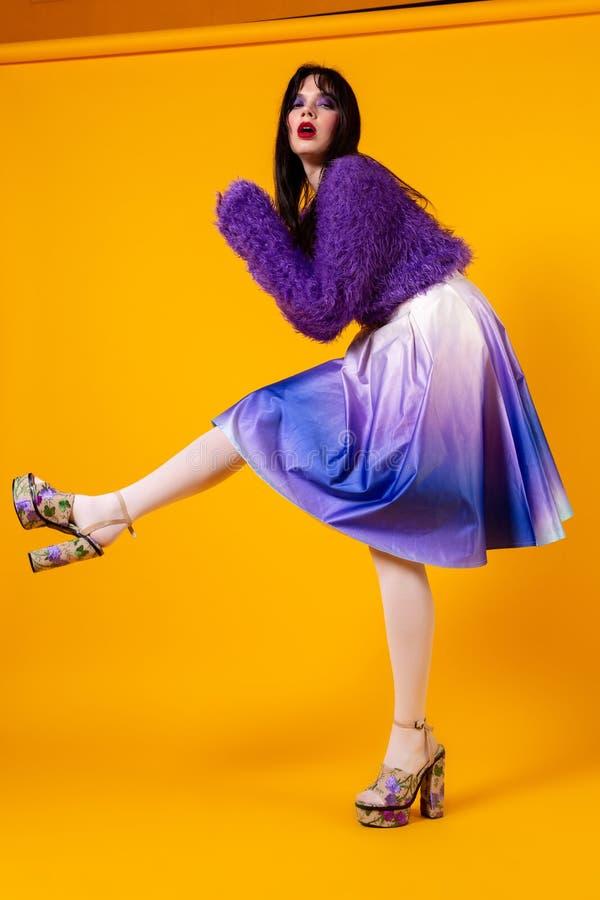 有被晒黑的皮肤跳舞的匀称夫人在橙色背景 免版税图库摄影
