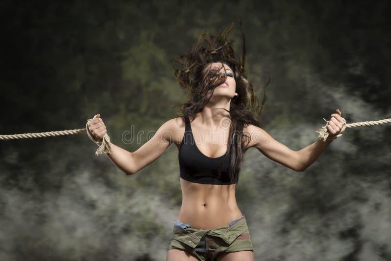 有被栓的腕子的坚强的妇女在性感的礼服 免版税库存图片