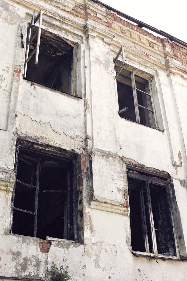 有被烧焦的木窗口的老被烧的房子 图库摄影