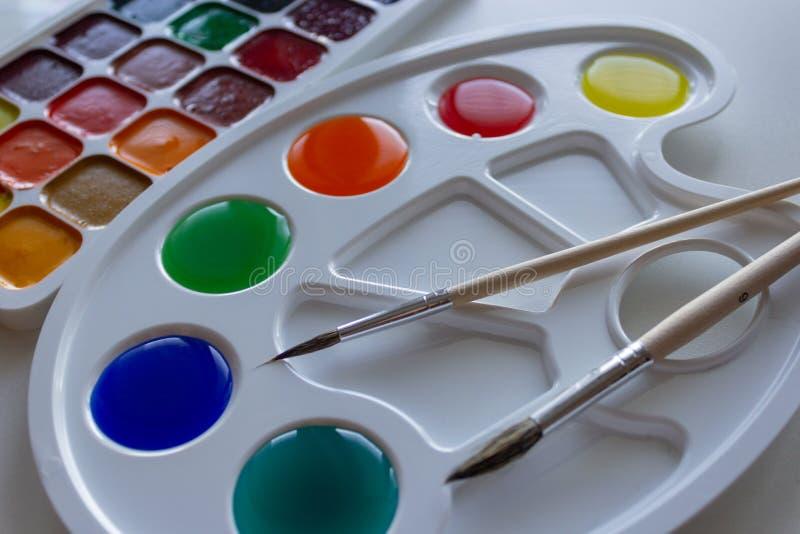 有被稀释的多彩多姿的油漆和两把刷子的调色板 免版税库存图片
