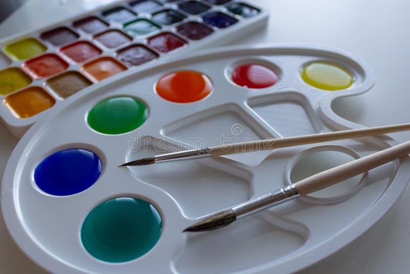 有被稀释的多彩多姿的油漆和两把刷子的调色板 库存图片