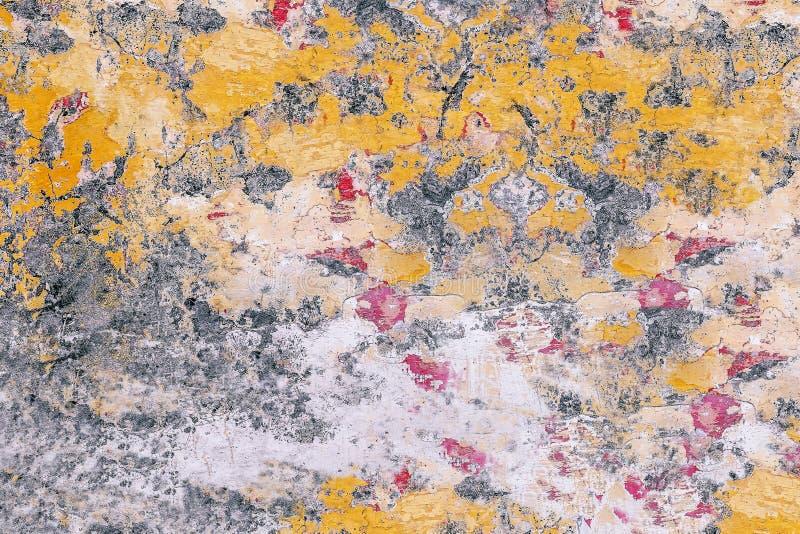 有被粉碎的油漆的老墙壁:在表面特写镜头的红色,黄色,灰色,白色斑点 免版税库存图片