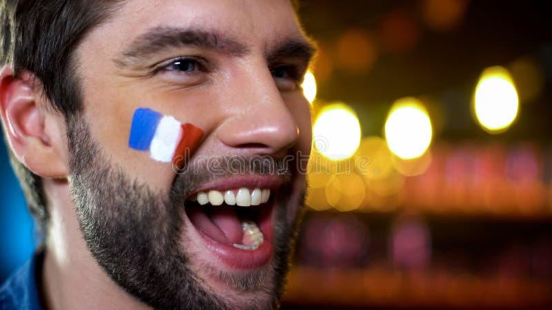 有被绘的旗子的愉快的英俊的有胡子的法国爱好者在面颊庆祝目标的 库存图片