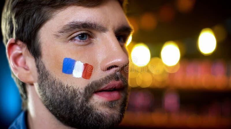 有被绘的法国旗子的严肃的人在电视的面颊观看的选举结果 库存图片