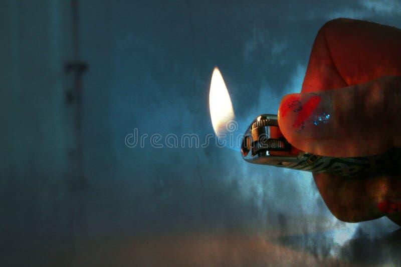 有被绘的钉子的一只woman's手在一个暗室拿着一个被点燃的打火机 免版税库存照片