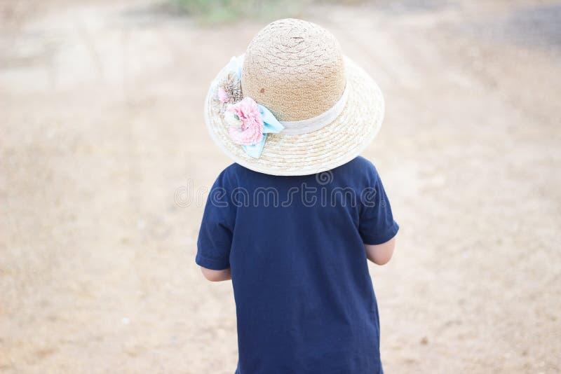 有被编织的帽子的男孩有木头的有被弄脏的背景,男孩走公开有迷离背景 图库摄影