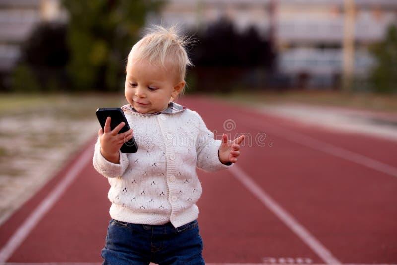 有被编织的成套装备的时兴的矮小的小孩男孩,走在  免版税库存图片