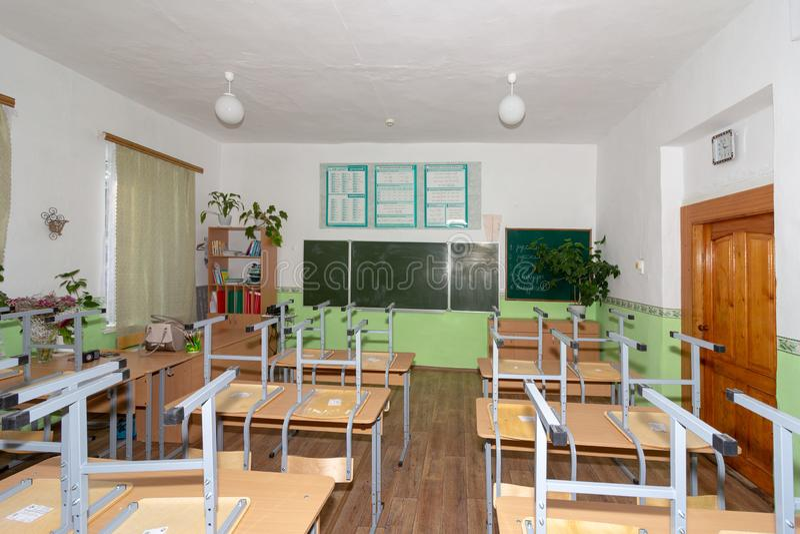 有被翻转的椅子的空的学校教室在乡校 免版税图库摄影