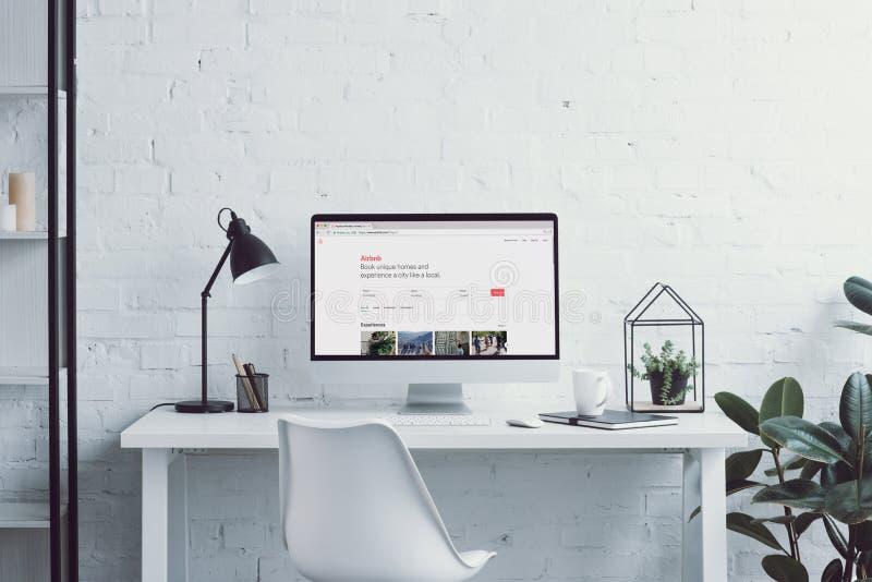 有被装载的airbnb页的计算机在桌上在现代办公室 库存图片