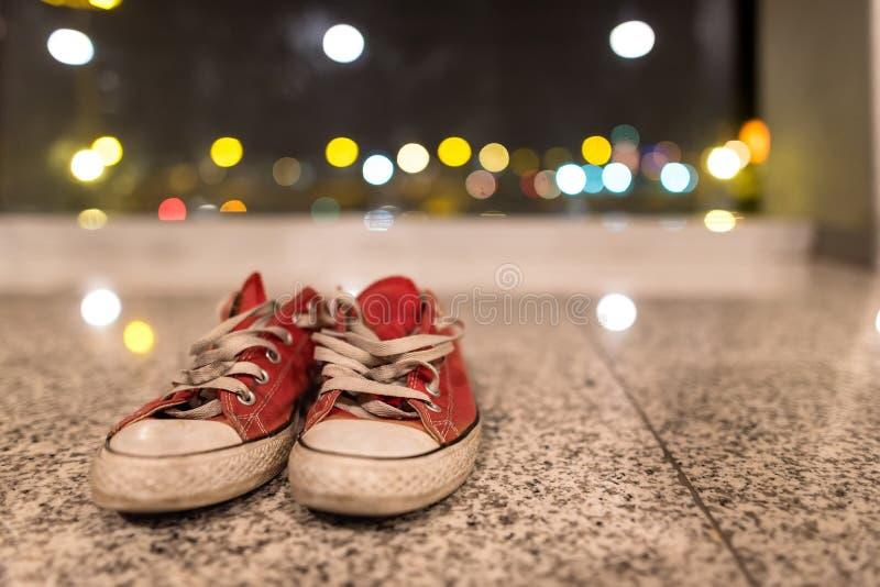有被解开的鞋带的老红色牛仔裤牛仔布侦探在被弄脏的背景 葡萄酒运动鞋 旅客成套装备 免版税库存图片