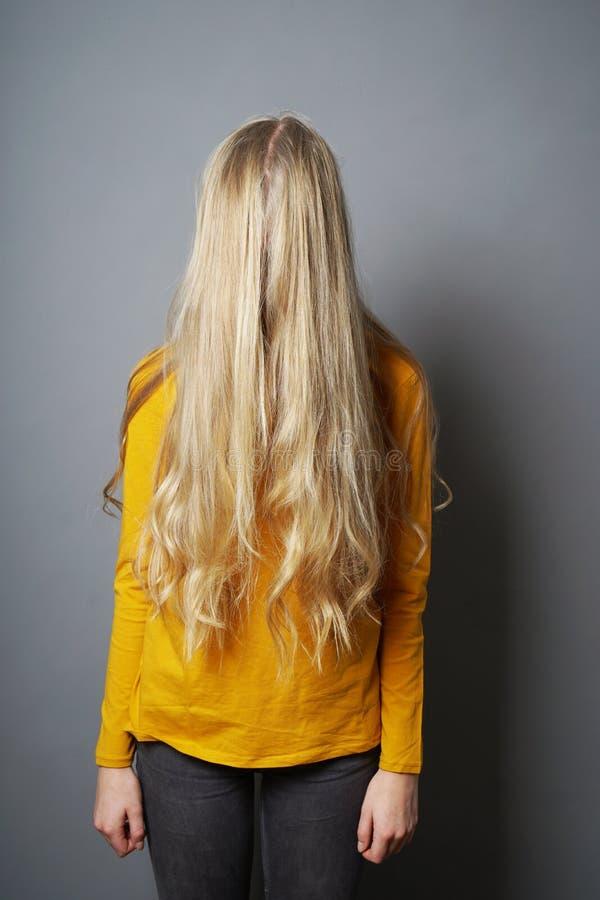 有被遮暗的面孔的害羞的年轻女人在长的金发后 库存图片