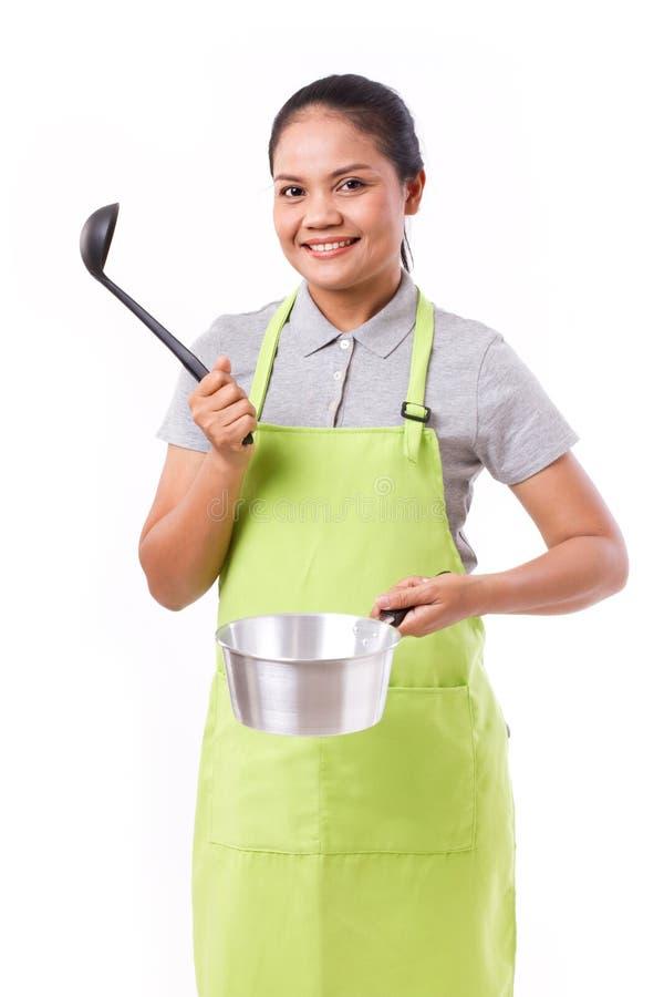 有被隔绝的围裙的亚裔烹调夫人 库存图片