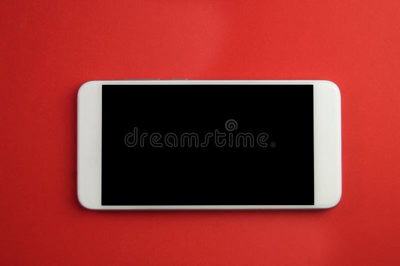 有被隔绝的屏幕的白色智能手机在红色 免版税库存照片