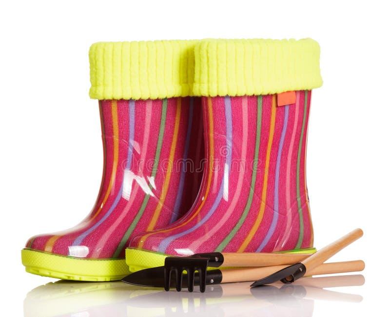 有被隔绝的织品插页、铁锹和犁耙的儿童胶靴 库存图片