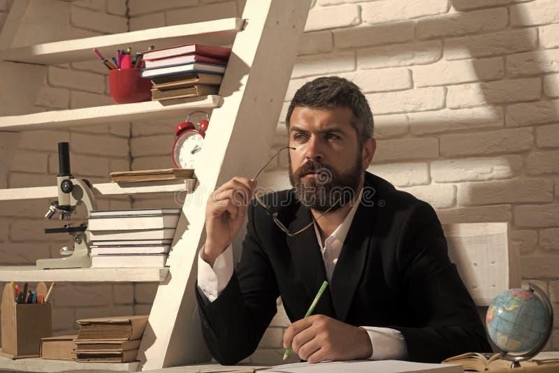 有被集中的面孔表示的教授坐在书桌 库存图片