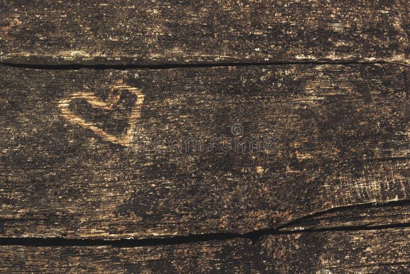 有被雕刻的心脏形状的老木板 免版税库存图片