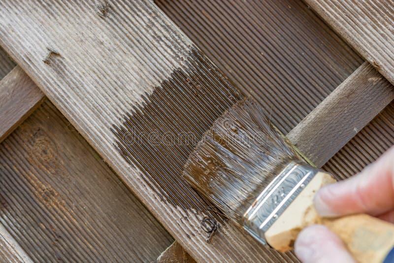 有被风化的老油漆的木篱芭得到与棕色釉的新的木保护 库存照片