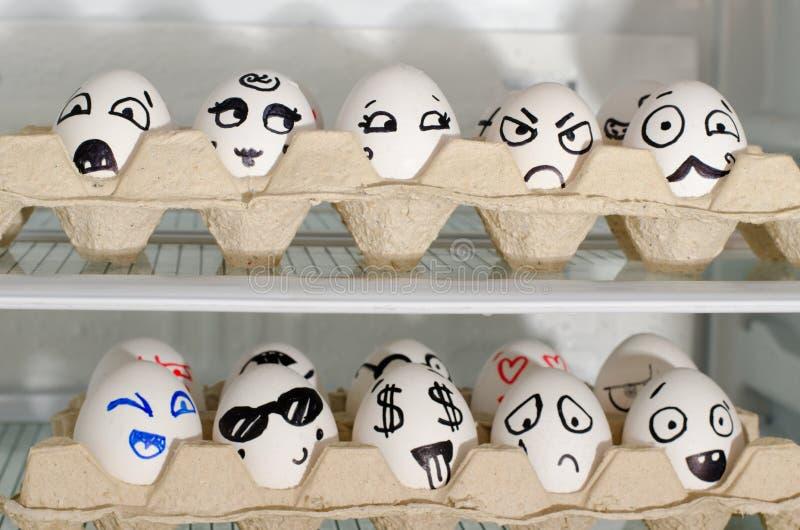 有被绘的微笑的两个盘子在冰箱架子的鸡蛋,关闭 免版税库存图片