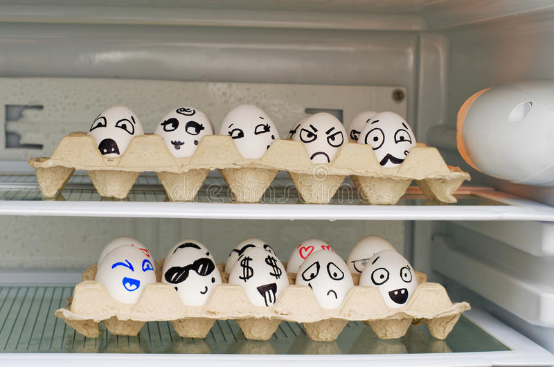 有被绘的微笑的两个盘子在冰箱的鸡蛋搁置 库存照片