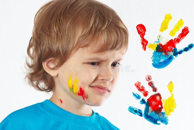 有被绘的面孔的不满意的男孩在手背景打印 免版税库存照片