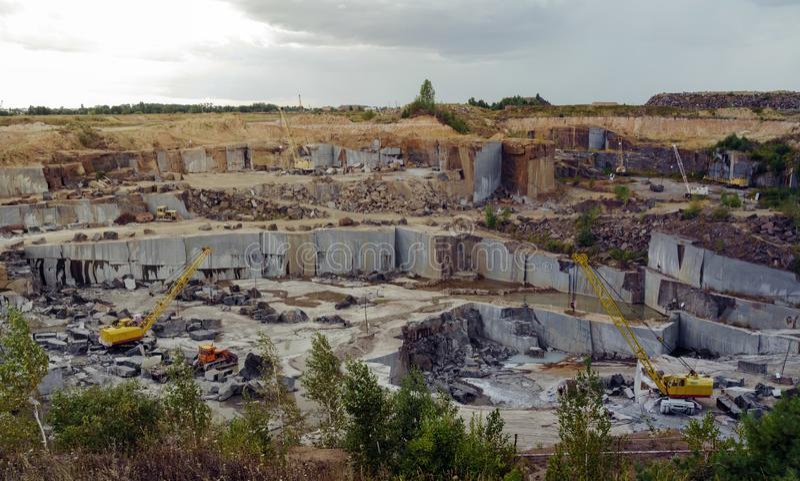 有装载未加工的岩石的重的设备挖掘机的花岗岩石矿 免版税库存照片