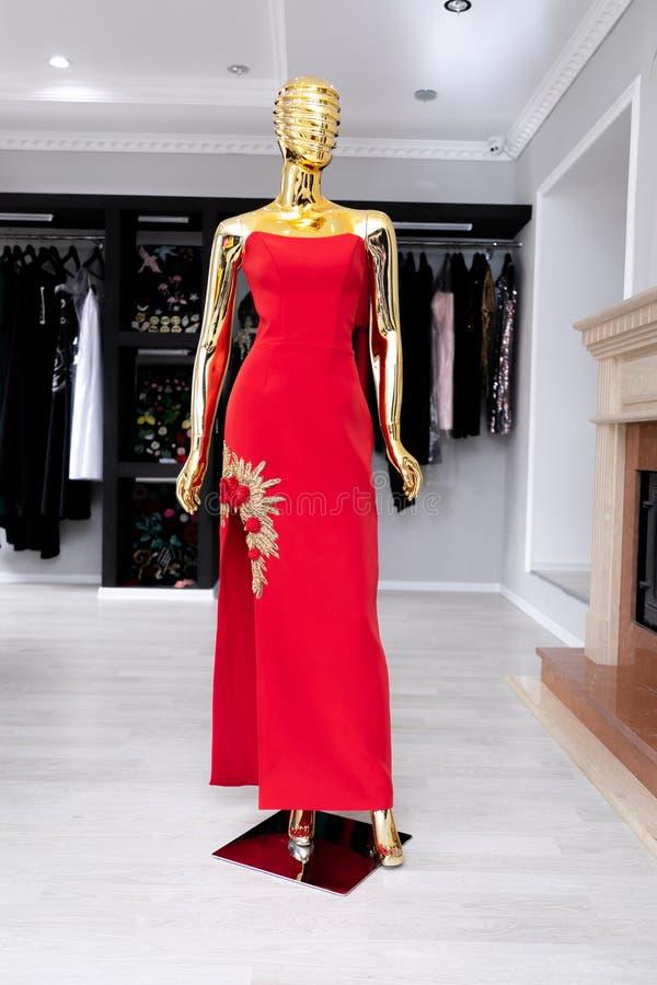 有装饰品的女性,长的红色礼服从在一个金黄时装模特的金黄小珠 免版税库存图片