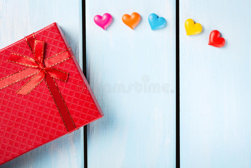 有装饰心脏的红色礼物盒在好的蓝色木背景 库存图片