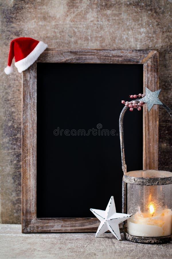 有装饰的圣诞节黑板 圣诞老人帽子,星,木 库存照片