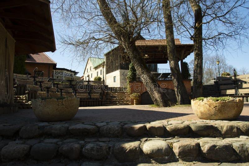 有装饰石花瓶老木房子的岩石台阶和一个砖墙有曲拱门背景 免版税图库摄影