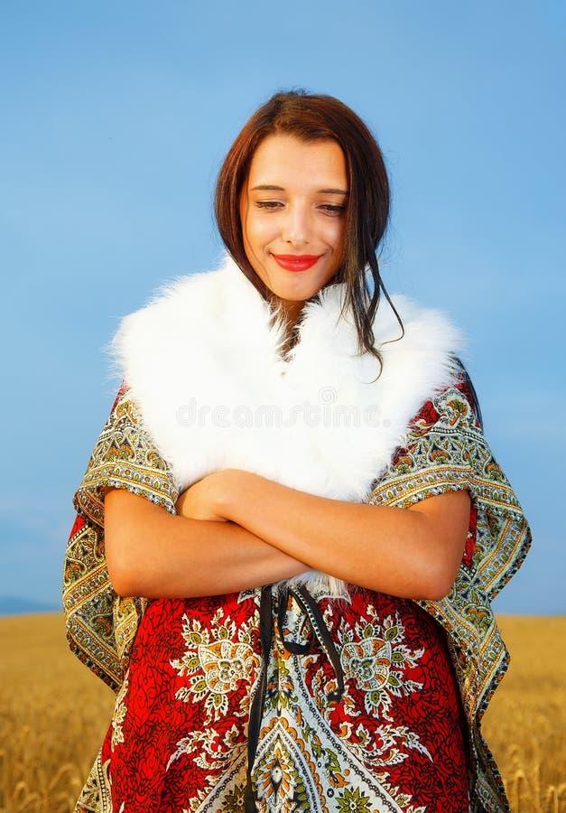 有装饰站立在与日落的一块麦田的礼服和白色毛皮的少妇 自然本底 库存图片