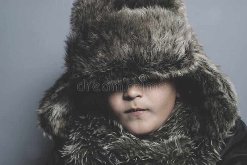 有裘皮帽的滑稽的孩子和冬天涂上,冷的概念和风暴 库存图片