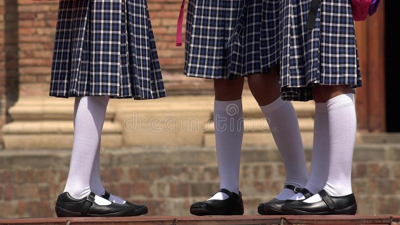 有裙子和白色袜子的天主教学校女孩 免版税库存照片