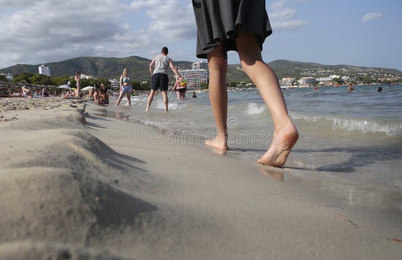 有裙子的女孩赤足走在magaluf海滩的 库存照片