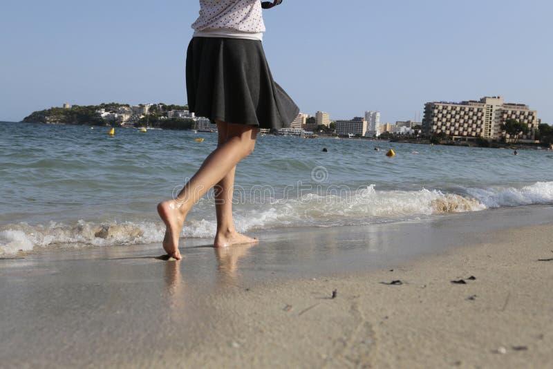 有裙子的赤足走的女孩magaluf海滩沙子  库存图片