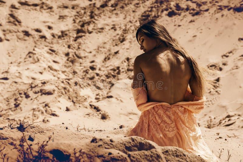 有裸体后面的华美的女孩坐沙子 库存图片