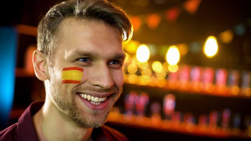 有西班牙旗子的微笑微笑的人在面颊,观看的全国竞争 库存照片