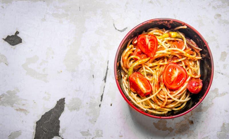 有西红柿酱、香料和蕃茄的意粉在碗 库存照片