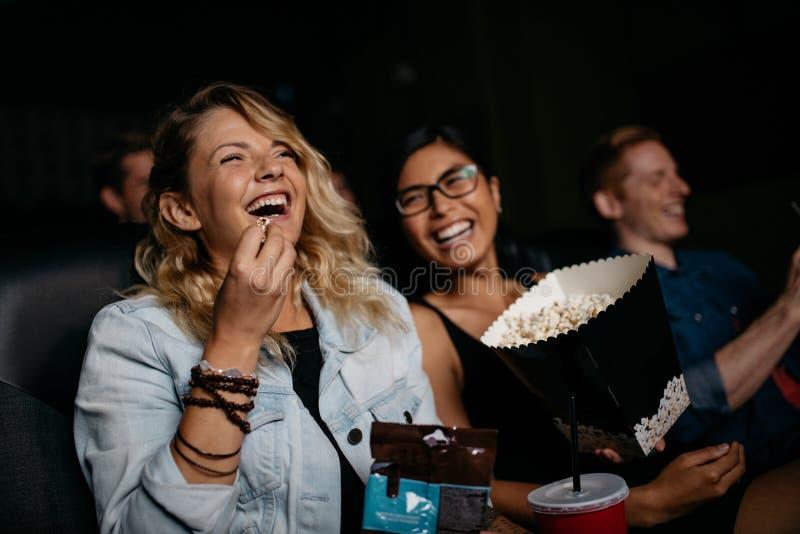 有观看电影的朋友的少妇 免版税库存照片