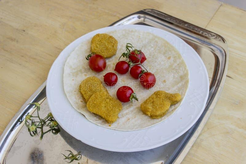 有角度的透视射击了鸡块和小红色新鲜的蕃茄在宽白色板材作为早餐 图库摄影