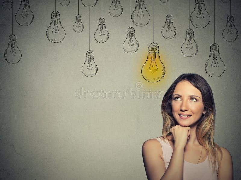 有解答电灯泡的愉快的聪明的女孩在头上 免版税图库摄影