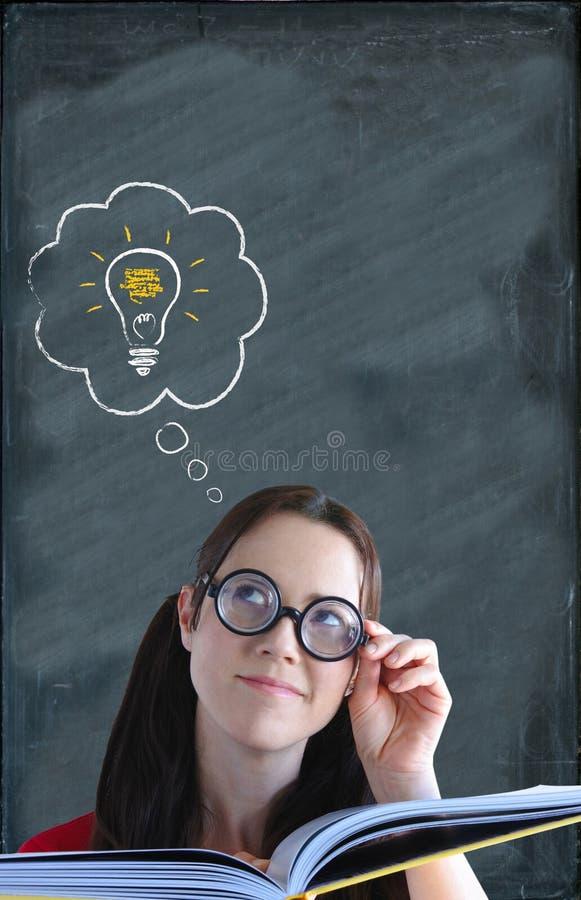有解答电灯泡的愉快的聪明的妇女在她的头上有a 免版税图库摄影