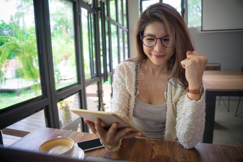 有触摸屏片剂计算机的少妇在咖啡馆 免版税图库摄影