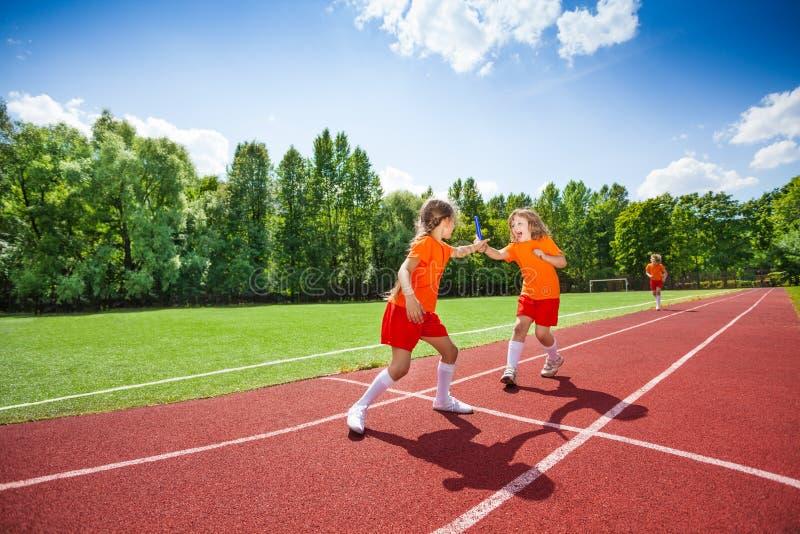 有警棒奔跑和手的女孩它对其他赛跑者 免版税库存图片
