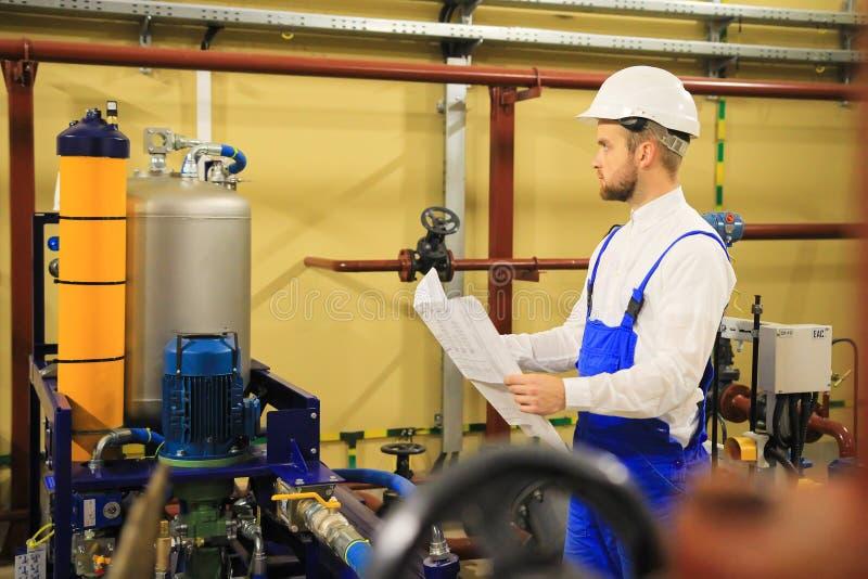 有计划的产业工人分析油泵设备的 库存照片