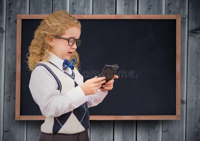 有计算器的女孩反对黑板和灰色木盘区 库存照片
